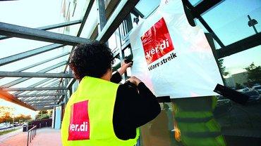"""Frau mit ver.di-Weste befestigt Plakat """"Warnstreik"""""""